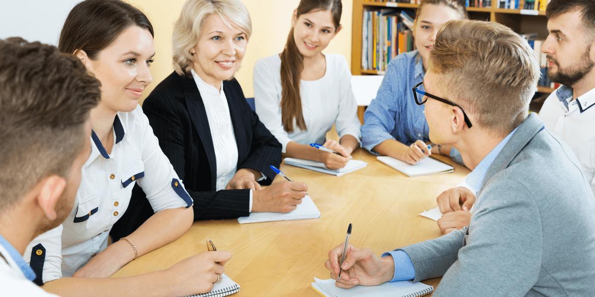 Gruppe aufmerksamer Studenten und Professorin, die im Auditorium zusammenarbeiten