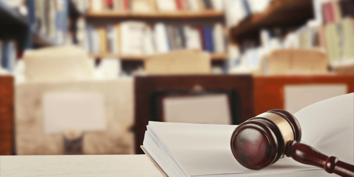 Hölzerner Richterhammer, der auf dem Gesetzbuch auf dem Tisch in der Bibliothek liegt