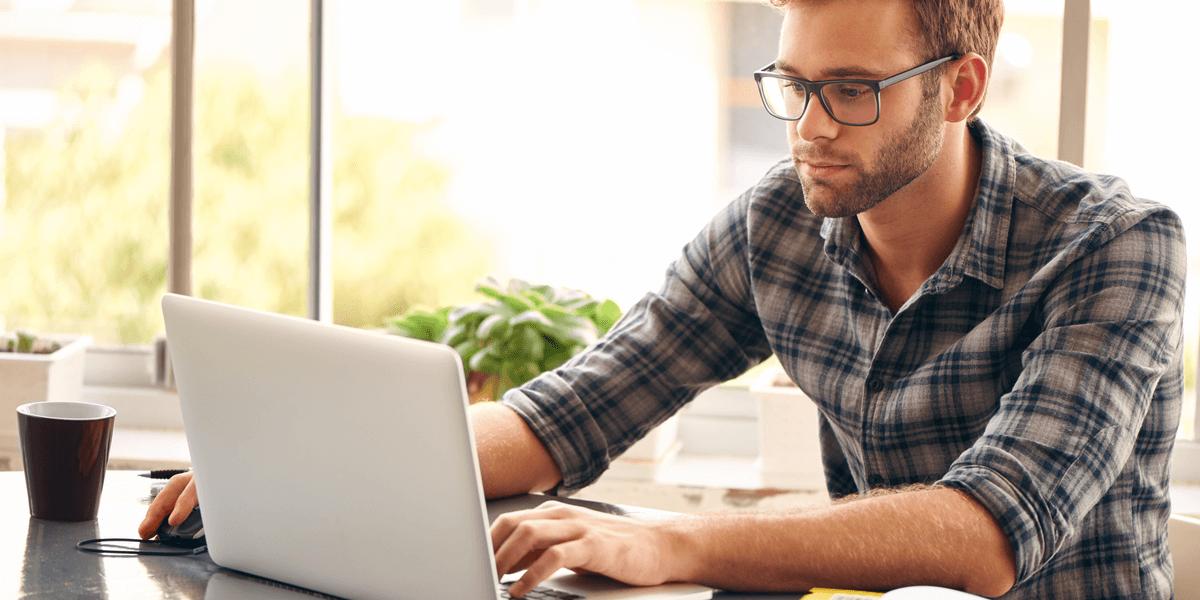 Ein junger Mann mit Brille arbeitet an seinem Laptop