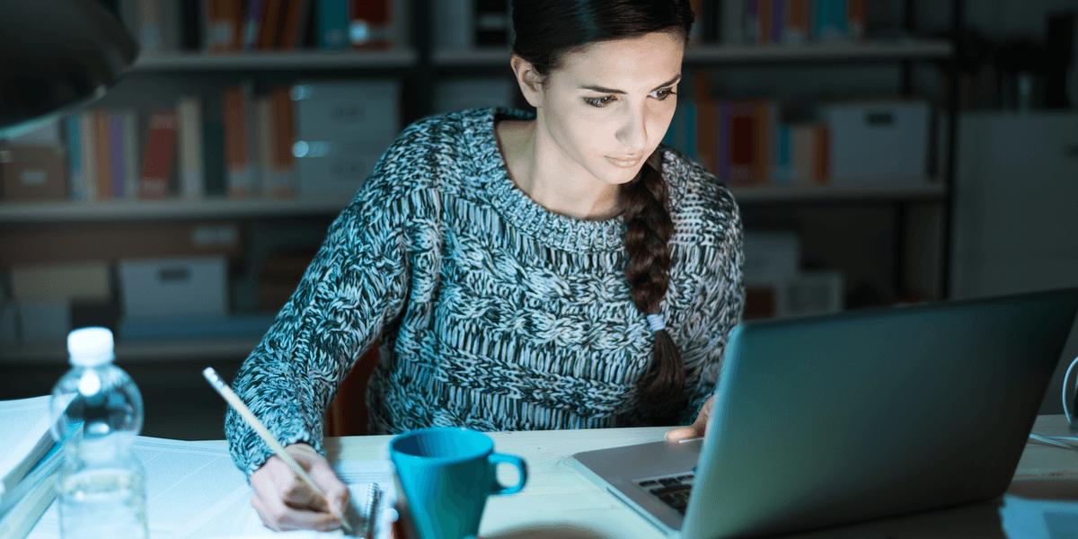 Junge Studentin, die zu Hause Hausaufgaben macht, schreibt und benutzt Laptop