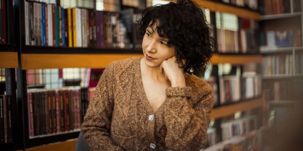 Frau in der Bibliothek, die ein Buch liest.