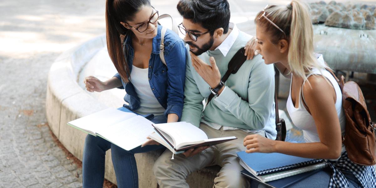 Glückliche Gruppe von Studenten, die zusammen studieren und lernen